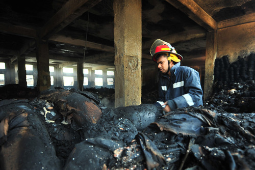 A Bangladeshi police official inspects the burnt garment factory in the Savar neighborhood outside Dhaka, Bangladesh, Sunday Nov. 25, 2012. At least 112 people were killed in a late Saturday night fire that raced through the multi-story garment factory just outside of Bangladesh's capital, an official said Sunday.(AP Photo/ khurshed Rinku)