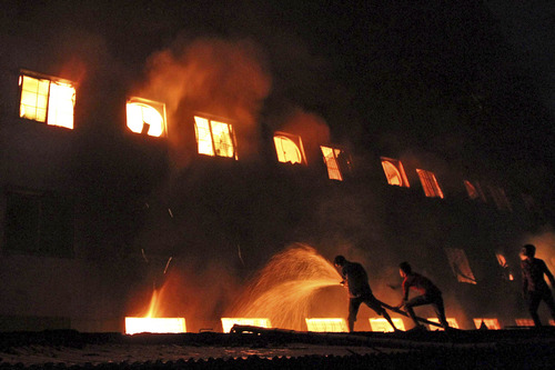 Bangladeshis and firefighters battle a fire at a garment factory in the Savar neighborhood in Dhaka, Bangladesh, late Saturday, Nov. 24, 2012. An official said firefighters have recovered more than 100 bodies after a fire raced through the multi-story garment factory just outside Bangladesh's capital. (AP Photo/Polash Khan)