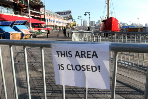 In this Friday, Nov. 23, 2012 photo, barricades close off a section of New York's South Street Seaport. The South Street Seaport, a popular tourist destination, remains a ghost town since the storm. (AP Photo/Tina Fineberg)