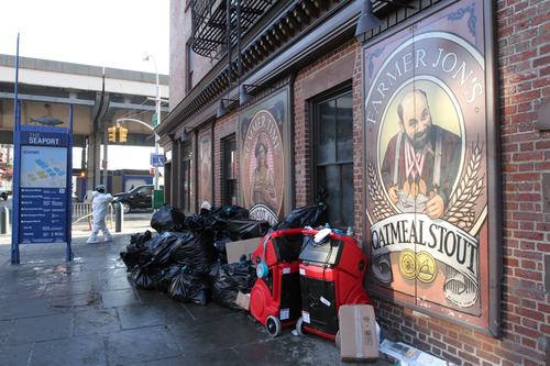 In this Friday, Nov. 23, 2012 photo, a worker wearing protective clothing enters the Heartland Brewery at New York's South Street Seaport, as bags of garbage from the Superstorm Sandy cleanup sit out front. The South Street Seaport, a popular tourist destination, remains a ghost town since the storm. (AP Photo/Tina Fineberg)