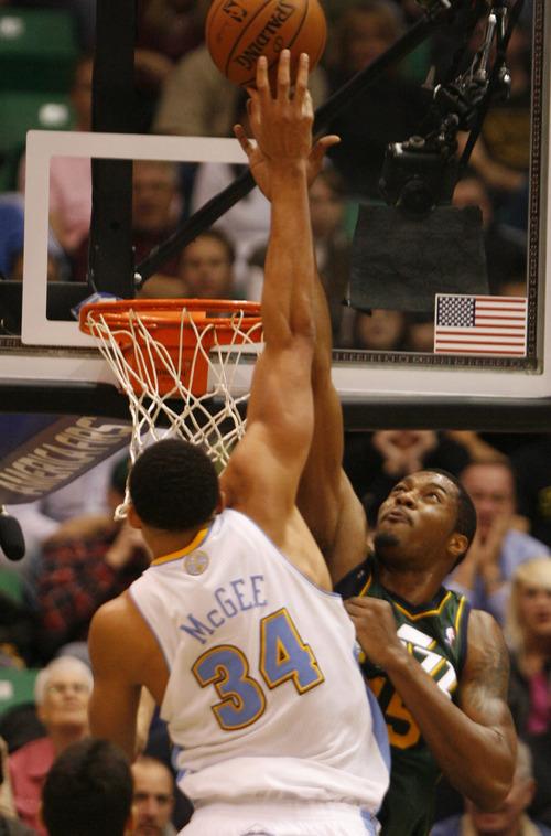 Rick Egan  | The Salt Lake Tribune   Denver Nuggets center JaVale McGee (34) shoots over Utah Jazz power forward Derrick Favors (15), as Utah defeated Denver 105-103 in NBA action, in Salt Lake City, Monday, November 26, 2012.