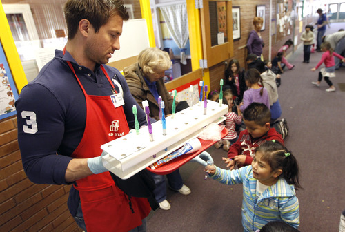 Al Hartmann  |  The Salt Lake Tribune Johnny Downard, lead Head Start teacher, hands out toothbrushes for children to use after eating lunch. They wash and brush after each meal at Neighborhood House, which has been serving families in Salt Lake City for years and has the state's only accredited, private, year-round nonprofit preschool.
