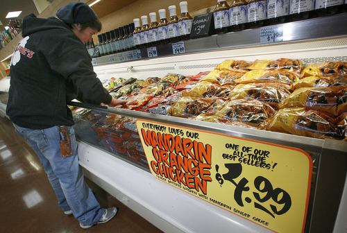 Scott Sommerdorf     The Salt Lake Tribune               AJ Biehler stocks one of the frozen food cabinets as she and others get Utah's first Trader Joe's store ready for opening day.