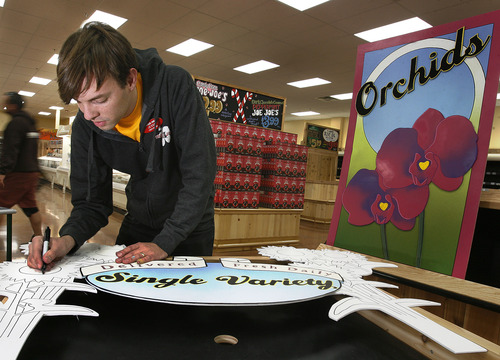 Scott Sommerdorf     The Salt Lake Tribune               Jesse Draper makes signs - this one for the floral department - as others stock and get Utah's first Trader Joe's store ready to open Nov. 30.