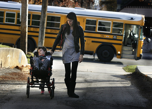 Scott Sommerdorf  |  The Salt Lake Tribune               Bertrand Might comes back from his day at the Ensign School in Salt Lake City, Monday, November 19, 2012. His mother, Cristina, walks alongside as he is pushed by his younger sister, Victoria.
