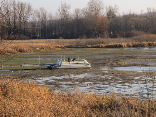 In this Nov. 16, 2012 photo, a stranded pontoon boat is docked at the eastern end of Portage Lake in the village of Onekama, Mich. Unusually low water levels on the Great Lakes are causing problems for boaters in small harbor towns such as Onekama, which is linked to Lake Michigan by a man-made channel. The Great Lakes, the world's biggest freshwater system, are dropping because of drought and climbing temperatures, a trend that accelerated with this year's almost snowless winter and scorching summer. (AP Photo/John Flesher)