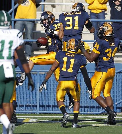 Kent State's Luke Wollet (39) celebrates with teammates after returning a fumble for a touchdown against Ohio during the first quarter of an NCAA college football game Friday, Nov. 23, 2012, in Kent, Ohio. Kent State won 28-6. (AP Photo/Ron Schwane)