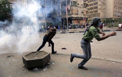 Egyptian protesters run for cover during clashes with security forces near Tahrir square, where an opposition rally has been called for to voice rejection of President Morsi's seizure of near absolute powers, in Cairo, Egypt, Tuesday, Nov. 27, 2012. Egyptian protesters and police clashed in Cairo on Tuesday just hours ahead of a planned massive rally by opponents of the country's Islamist president demanding he rescind decrees that granted him near-absolute powers. (AP Photo/ Khalil Hamra)