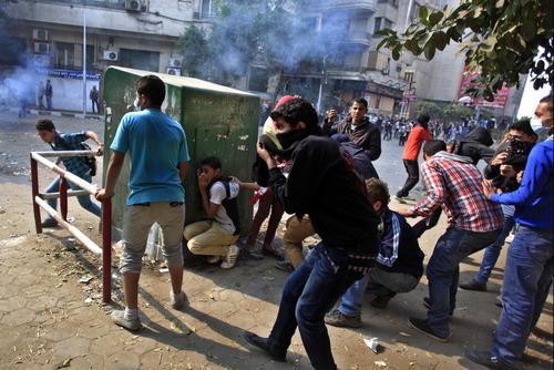 Egyptian protesters take cover during clashes with security forces near Tahrir square, where an opposition rally has been called for to voice rejection of President Morsi's seizure of near absolute powers, in Cairo, Egypt, Tuesday, Nov. 27, 2012. Egyptian protesters and police clashed in Cairo on Tuesday just hours ahead of a planned massive rally by opponents of the country's Islamist president demanding he rescind decrees that granted him near-absolute powers. (AP Photo/Khalil Hamra)
