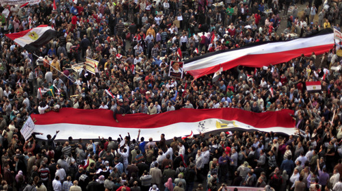 Egyptian protesters carry large national flags in Tahrir Square in Cairo, Egypt, Tuesday, Nov. 27, 2012. Thousands flocked to Cairo's central Tahrir square on Tuesday for a protest against Egypt's president in a significant test of whether the opposition can rally the street behind it in a confrontation aimed at forcing the Islamist leader to rescind decrees that granted him near absolute powers. (AP Photo/ Khalil Hamra)