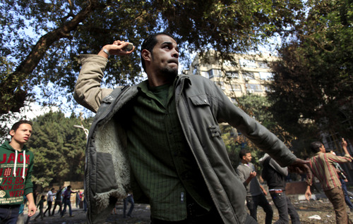 Egyptian protesters clash with security forces near Tahrir square, where an opposition rally has been called for to voice rejection of President Morsi's seizure of near absolute powers, in Cairo, Egypt, Tuesday, Nov. 27, 2012. Egyptian protesters and police clashed in Cairo on Tuesday just hours ahead of a planned massive rally by opponents of the country's Islamist president demanding he rescind decrees that granted him near-absolute powers.(AP Photo/ Khalil Hamra)