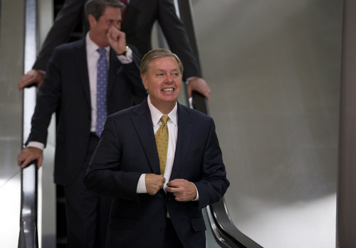 Sen. Lindsey Graham, R-S.C., adjusts his jacket as he walks to his office on Capitol Hill in  Washington, Wednesday, Nov. 28, 2012.  (AP Photo/ Evan Vucci)