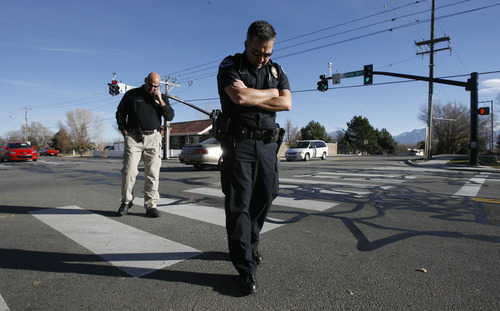Francisco Kjolseth  |  The Salt Lake Tribune Detective Sam Winkler, left, and officer Mark Wright with the South Jordan police department, investigate the corner of 4000 West and 9800 South where Elk Ridge Middle School P.E. teacher Randy Treglown, 51, was struck and killed by a car as he jogged to work early Wednesday, November 28, 2012.