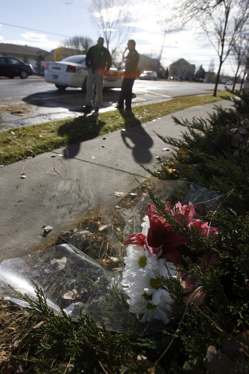 Francisco Kjolseth  |  The Salt Lake Tribune Flowers placed at the scene of an accident mark where Detective Sam Winkler and officer Mark Wright with the South Jordan police department investigate where Elk Ridge Middle School P.E. teacher Randy Treglown, 51, was struck and killed by a car at the corner of 4000 West and 9800 South as he jogged to work early Wednesday, November 28, 2012.