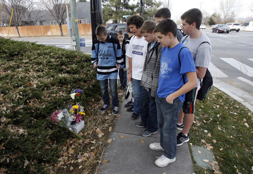 "Francisco Kjolseth  |  The Salt Lake Tribune Winston Schoeneweis, 13, foreground, joins fellow students from Elk Ridge Middle School in South Jordan to reflect on their P.E. teacher Randy Treglown, 51, who was stuck and killed by a car at the corner of 4000 West and 9800 South as he jogged to work early Wednesday, November 28, 2012. ""He was a great teacher, he was the only person that got me to run,"" said Schoeneweis as they visited the makeshift memorial."