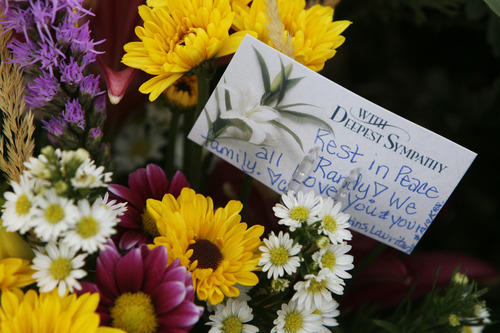 Francisco Kjolseth  |  The Salt Lake Tribune Flowers and notes make up a makeshift memorial for Elk Ridge Middle School P.E. teacher Randy Treglown, 51, at the intersection where he was struck and killed by a car at the corner of 4000 West and 9800 South as he jogged to work early Wednesday, November 28, 2012.