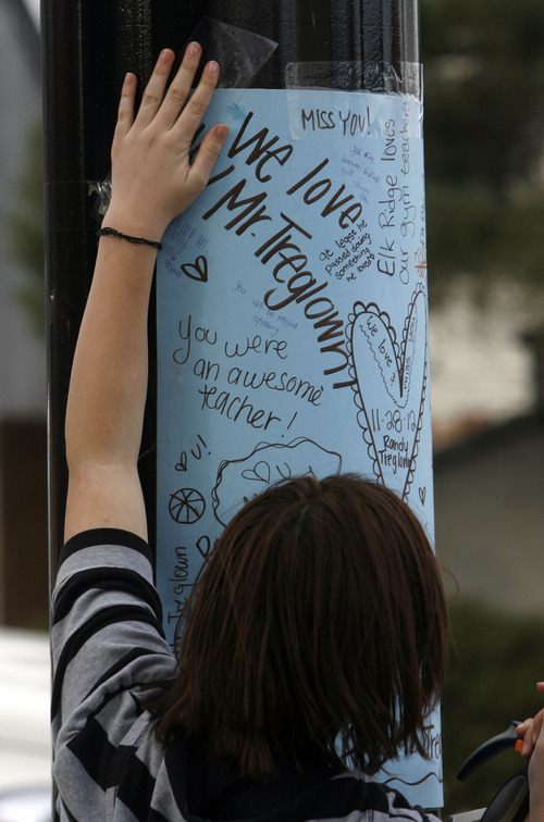 Francisco Kjolseth  |  The Salt Lake Tribune Cassidy Blackham, 15, joins fellow classmates as they erect a makeshift memorial for Elk Ridge Middle School P.E. teacher Randy Treglown, 51, at the intersection where he was struck and killed by a car at the corner of 4000 West and 9800 South as he jogged to work early Wednesday, November 28, 2012.