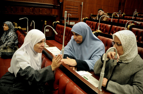Azza el-Gharf of the Muslim Brotherhood's Freedom and Justice Party, second left, speaks with other members of the assembly during the vote on a final draft of a new Egyptian constitution in Cairo, Egypt, Thursday, Nov. 29, 2012. The assembly, overwhelmingly made up of allies of President Mohammed Morsi, abruptly moved up the vote which hadn't been expected to take place for another two months in order to pass the draft before Egypt's Supreme Constitution Court rules on Sunday on whether to dissolve the panel. (AP Photo/Mohammed Asad)