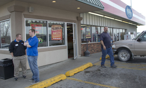 An unidentified customer walks out of the  Trex Mart convenience store, right, while manager Chris Nauerz, left, and son of the owner Baron Hartell stand outside, in Dearborn, Mo., Thursday, Nov. 29, 2012. Lottery officials confirmed Thursday that one of two winning Powerball tickets sold before Wednesday's drawing was bought at a Trex Mart convenience store in Dearborn. (AP Photo/Orlin Wagner)