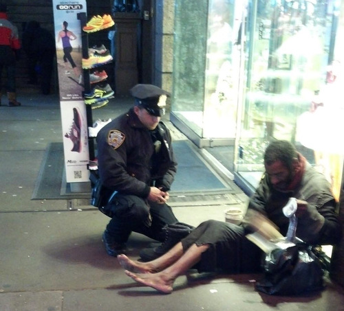 """This photo provided by Jennifer Foster shows New York City Police Officer Larry DePrimo presenting a barefoot homeless man in New York's Time Square with boots Nov. 14, 2012 . Foster was visiting New York with her husband on Nov. 14, when she came across the shoeless man asking for change in Times Square. As she was about to approach him, she said the officer  came up to the man with a pair of all-weather boots and thermal socks on the frigid night. She took the picture on her cellphone. It was posted Tuesday night to the NYPD's official Facebook page and became an instant hit. More than 350,000 users """"liked"""" it as of Thursday afternoon, and over 100,000 shared it. (AP Photo/Jennifer Foster)"""