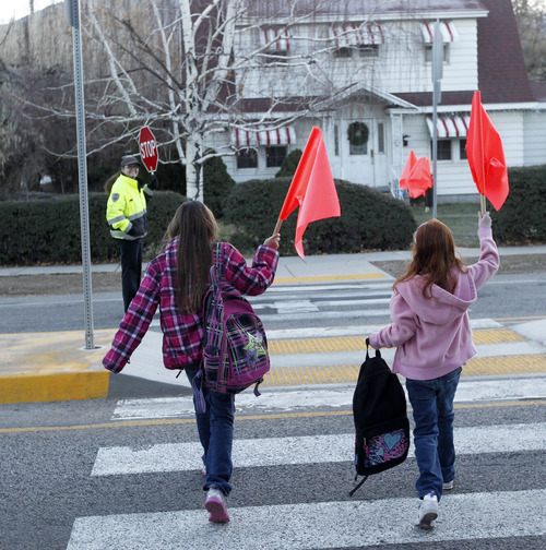 Al Hartmann  |  The Salt Lake Tribune Two girls bound for Rosecrest Elementary School held orange flags high Tuesday morning as they crossed 2300 East at 3000 South.   Salt Lake County is putting orange flags at four crosswalks in Millcreek, a pilot project that could spread to other areas of the unincorporated county.