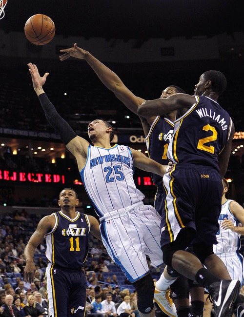 New Orleans Hornets guard Austin Rivers (25) drives to the basket against Utah Jazz forward Marvin Williams (2) and forward Derrick Favors in the first half of an NBA basketball game in New Orleans, Wednesday, Nov. 28, 2012. (AP Photo/Gerald Herbert)