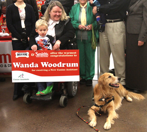 Rick Egan  | The Salt Lake Tribune  Wanda Woodrum, of Pleasant Grove, with 3-year-old Jacob Averett on her lap, gathers with her family and friends Thursday to meet Barnsley, the ambassador dog for Canine Assistants, at Smith's in Provo. Woodrum will receive her dog in January 2013 when she travels to Alpharetta, Ga., for a two-week training camp.