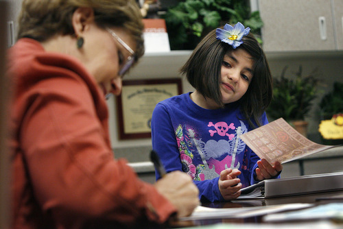 """Scott Sommerdorf     The Salt Lake Tribune              Student Valerie Uribe watches proudly as Principal Karen Thomson makes out her award certificate for this month's """"The Leader in Me"""" winners at Falcon Ridge Elementary. This school year is its second to implement """"The Leader in Me"""" program, Franklin Covey's educational program in which kids are taught daily how to use the """"7 habits of highly successful people."""""""