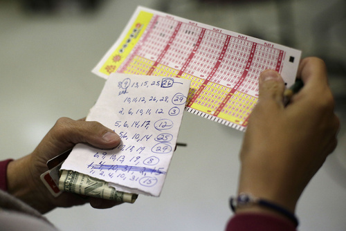 """Sharon Long double checks her Powerball numbers as she stands in line in a convenience store in Baltimore, Wednesday, Nov. 28, 2012. Long, a customer service representative for a plumbing company, picked numbers that her sister asked her to play with. If she wins the jackpot with her sister's numbers, """"I'm not sharing,"""" she jokingly added. (AP Photo/Patrick Semansky)"""