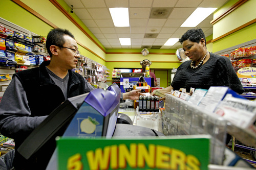 """Benita Lewis, 41, of Atlanta, right, buys a Powerball lottery ticket from store worker Bryant Kim, at a convenience store, Wednesday, Nov. 28, 2012, in Atlanta. """"I did feel nervous buying it like I could be the one,"""" says Lewis. """"I'm going to retire and pay off all my family's debt, immediate family, I got to that back, immediate family's debt."""" (AP Photo/David Goldman)"""