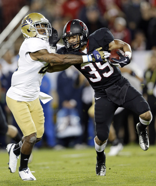 Stanford running back Kelsey Young (39) is brought down by UCLA defensive back Brandon Sermons during the first half of the Pac-12 championship NCAA college football game in Stanford, Calif., Friday, Nov. 30, 2012. (AP Photo/Marcio Jose Sanchez)