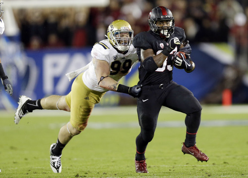 Stanford running back Stepfan Taylor (33) runs past UCLA defensive end Cassius Marsh (99) during the first half of the Pac-12 championship NCAA college football game in Stanford, Calif., Friday, Nov. 30, 2012. (AP Photo/Marcio Jose Sanchez)