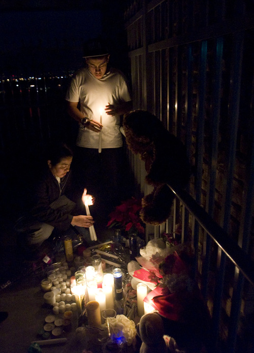 Kim Raff  |  The Salt Lake Tribune (from left) Celina Sorto and her son Frank stand by a memorial during a vigil for a 14-year-old student who committed suicide outside of the school on the pedestrian bridge near Bennion Junior High School in Taylorsville on Nov. 29, 2012. The student was good friends with the Sorto family.
