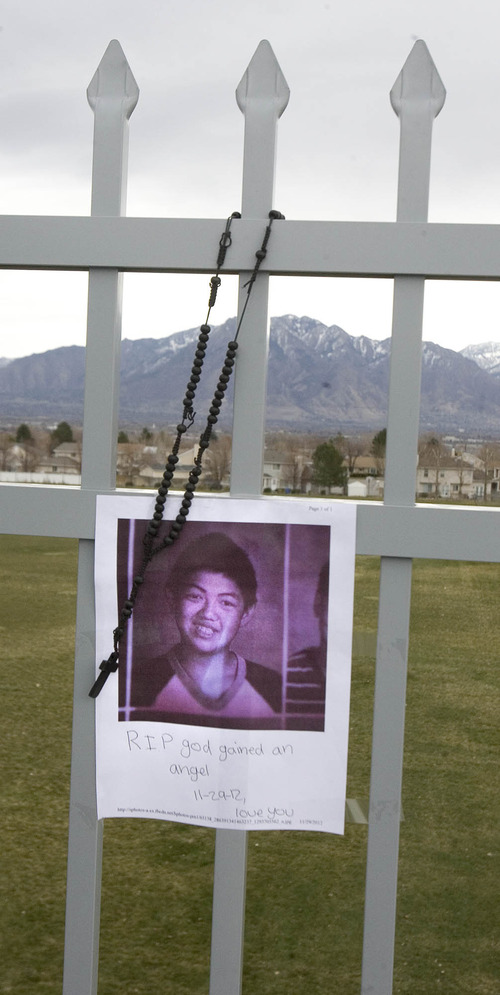 Paul Fraughton  |  The Salt Lake Tribune A photo of David Q. Phan and a rosary hangs Friday on the pedestrian walkway at 6200 South and 2700 West, where the 14-year-old fatally shot himself Thursday.