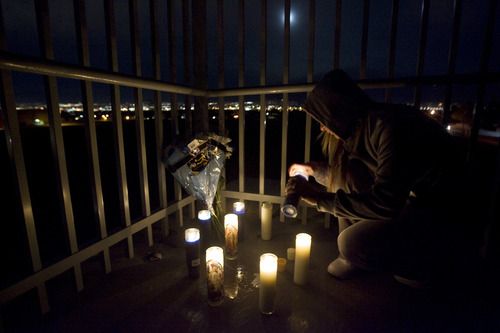 Kim Raff  |  The Salt Lake Tribune Angie McQuiston lights candles at a memorial on the pedestrian bridge in the place where a 14-year-old student committed suicide after school at Bennion Junior High in Taylorsville on Nov. 29, 2012.