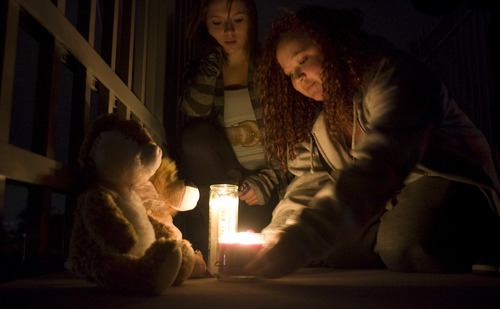 Kim Raff  |  The Salt Lake Tribune  (from left) Maiadae Werrett and Mia Kersey light candles at a memorial for a 14-year-old student who committed suicide outside of the school on the pedestrian bridge near Bennion Junior High  in Taylorsville on Nov. 29, 2012.