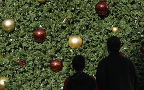 FILE - In this Friday, Nov. 23, 2012, file photo, two Black Friday shoppers walk past a large Christmas Tree at Union Square in San Francisco. A horrific fire that killed 112 people, Saturday, Nov. 24, 2012, at a Bangladesh garment factory owned by Tazreen Fashions Ltd has put the spotlight back on those factory workers and their sometimes treacherous work environment. The factory made clothing for several retailers around the globe including Wal-Mart, Sears and The Walt Disney Co. The companies said they didn't know the vendors were using the factory and according to a report by the Associated Press, holiday shoppers have also buffered themselves from the tragedy. (AP Photo/Jeff Chiu)