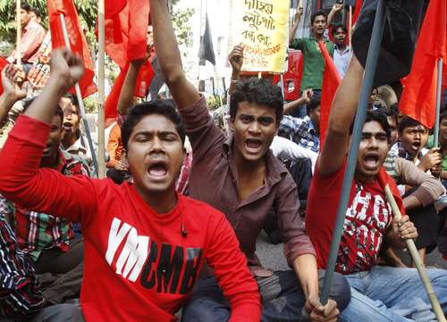 "Bangladeshi garment workers shout slogans as they participate in a protest to mourn the death of the victims of a fire in a garment factory in Dhaka, Bangladesh, Friday, Nov. 30, 2012. Hundreds of garment workers protested Friday outside the Bangladeshi factory where 112 people were killed by the fire, demanding compensation for their lost salaries. The placard behind reads: ""Stop looting from the garment sector."" (AP Photo/Pavel Rahman)"