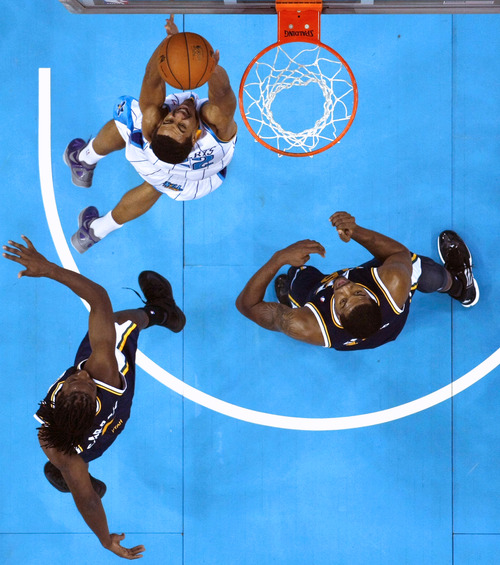 New Orleans Hornets guard Brian Roberts drives to the basket between Utah Jazz forward DeMarre Carroll, bottom left, and forward Derrick Favors, in the second half of an NBA basketball game in New Orleans, Wednesday, Nov. 28, 2012. The Jazz won 96-84. (AP Photo/Gerald Herbert)