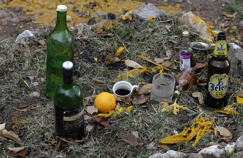 In this Nov. 30, 2012 photo, drinks are left on the grave of a deceased man,  in the village of Zarozje, near the Serbian town of Bajina Basta. Get your garlic, wooden crosses and stakes ready: a bloodsucking vampire is on the loose.  Or so say villagers in the tiny western Serbian hamlet of Zarozje, nestled between the lush green mountain slopes and spooky thick forests. Rumors that a legendary vampire ghost has returned are spreading panic throughout the town. An official warning telling villagers to put garlic in their pockets and place wooden crosses in each of their rooms, the tools that should keep away the vampires  did nothing but fuel the fear. (AP Photo/Darko Vojinovic)
