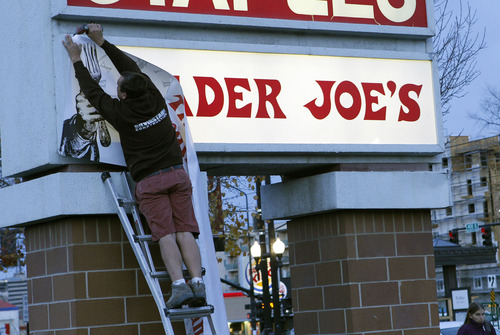 Al Hartmann  |  The Salt Lake Tribune Trader Joe's employee takes down opening soon banner to reveal the company sign at 634 East 400 South in Salt Lake City minutes before the grand opening Friday November 30 at 8 a.m.