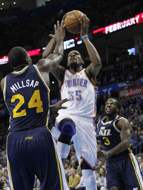 Oklahoma City Thunder forward Kevin Durant (35) shoots between Utah Jazz forwards Paul Millsap (24) and DeMarre Carroll (3) in the first quarter of an NBA basketball game in Oklahoma City, Friday, Nov. 30, 2012. (AP Photo/Sue Ogrocki)