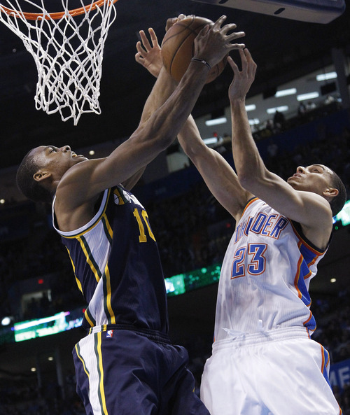 Utah Jazz guard Alec Burks (10) and Oklahoma City Thunder guard Kevin Martin (23) go up for a rebound in the fourth quarter of an NBA basketball game in Oklahoma City, Friday, Nov. 30, 2012. Oklahoma City won 106-94. (AP Photo/Sue Ogrocki)