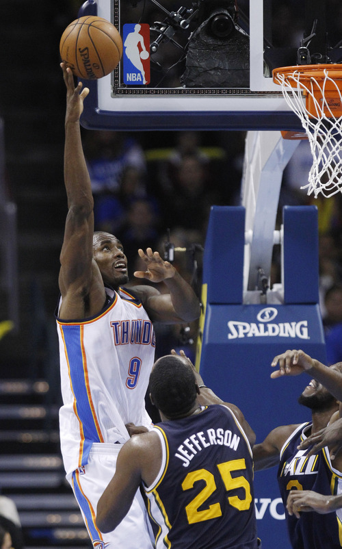 Oklahoma City Thunder forward Serge Ibaka (9) shoots in front of Utah Jazz center Al Jefferson and guard Jamaal Tinsley, right, in the third quarter of an NBA basketball game in Oklahoma City, Friday, Nov. 30, 2012. Oklahoma City won 106-94. (AP Photo/Sue Ogrocki)