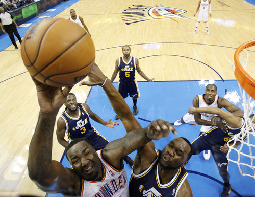Oklahoma City Thunder center Kendrick Perkins, left, shoots in front of Utah Jazz center Al Jefferson, right, in the first quarter of an NBA basketball game in Oklahoma City, Friday, Nov. 30, 2012. Oklahoma City won 106-94. (AP Photo/Sue Ogrocki)
