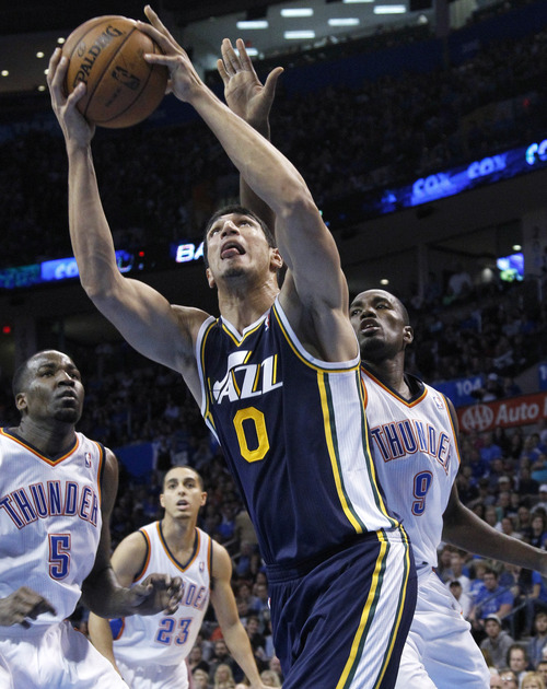 Utah Jazz center Enes Kanter (0) shoots in front of Oklahoma City Thunder center Kendrick Perkins (5), guard Kevin Martin (23) and guard Russell Westbrook (0) during the fourth quarter of an NBA basketball game in Oklahoma City, Friday, Nov. 30, 2012. Oklahoma City won 106-94. (AP Photo/Sue Ogrocki)
