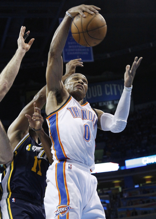 Oklahoma City Thunder guard Russell Westbrook (0) grabs a rebound in front of Utah Jazz guard Earl Watson (11) i the fourth quarter of an NBA basketball game in Oklahoma City, Friday, Nov. 30, 2012. Oklahoma City won 106-94. (AP Photo/Sue Ogrocki)