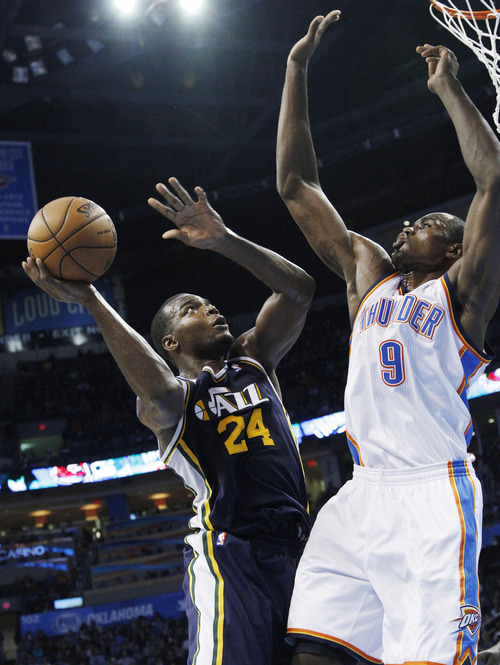Utah Jazz forward Paul Millsap shoots in front of Oklahoma City Thunder forward Serge Ibaka (9) during the third quarter of an NBA basketball game in Oklahoma City, Friday, Nov. 30, 2012. Oklahoma City won 106-94. (AP Photo/Sue Ogrocki)