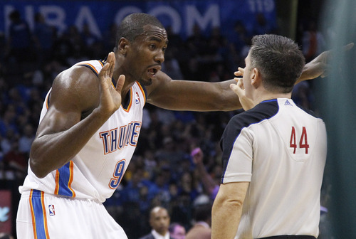 Oklahoma City Thunder forward Serge Ibaka talks with official Eli Roe (44) after a foul call in the third quarter of an NBA basketball game against the Utah Jazz in Oklahoma City, Friday, Nov. 30, 2012. Oklahoma City won 106-94. (AP Photo/Sue Ogrocki)