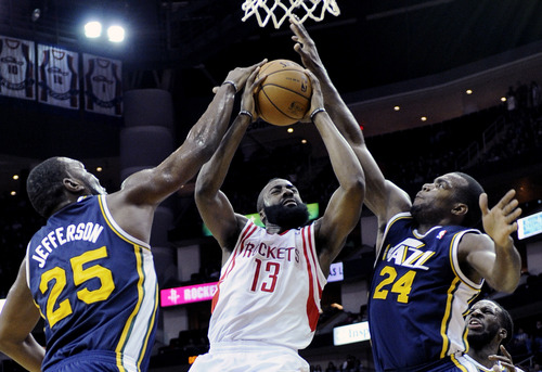 Houston Rockets' James Harden (13) goes to the basket while double-teamed by Utah Jazz Al Jefferson (25) and Paul Millsap (24) in the first half of an NBA basketball game on Saturday, Dec. 1, 2012, in Houston. (AP Photo/Pat Sullivan)